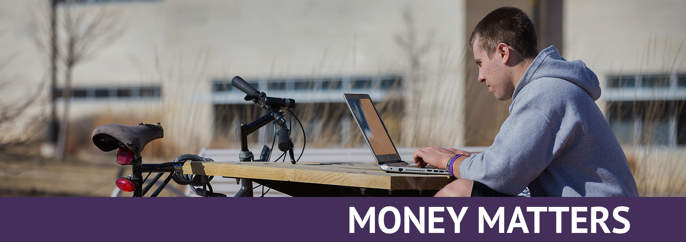 Money Matters: Student working at a laptop outside
