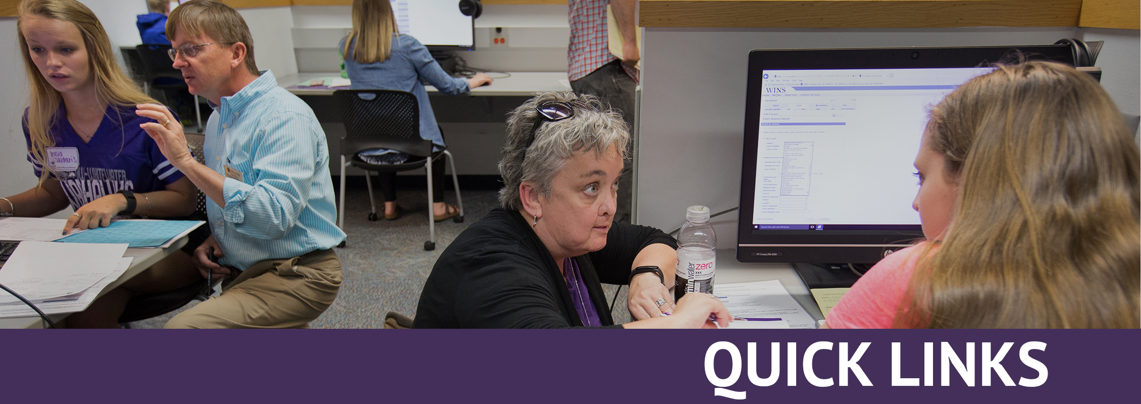 Quick Links: Instructors helping students, one at a computer
