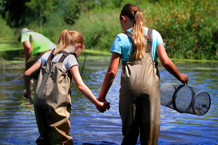 Image: Two adolescents standing in a small lake with waders