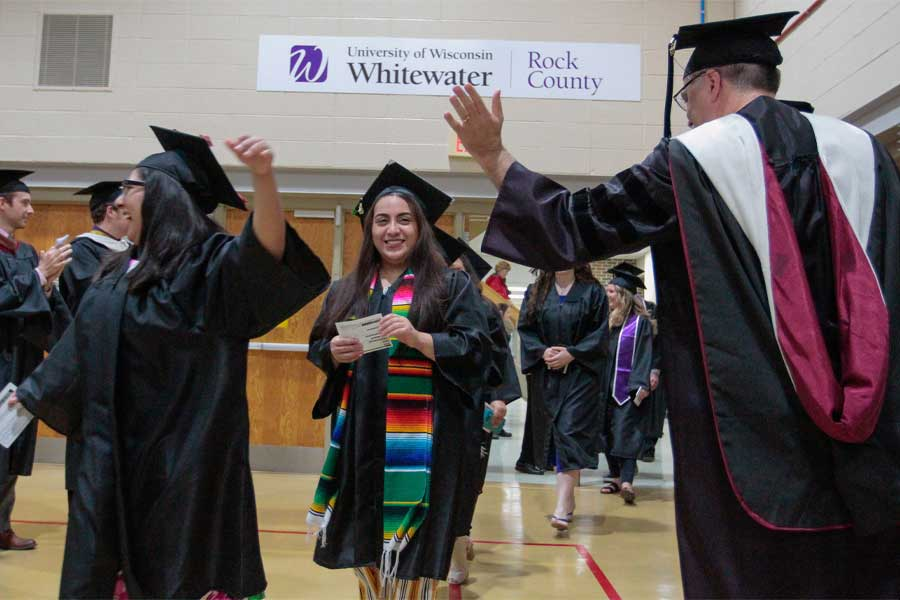 Students at commencement are cheered on by faculty.