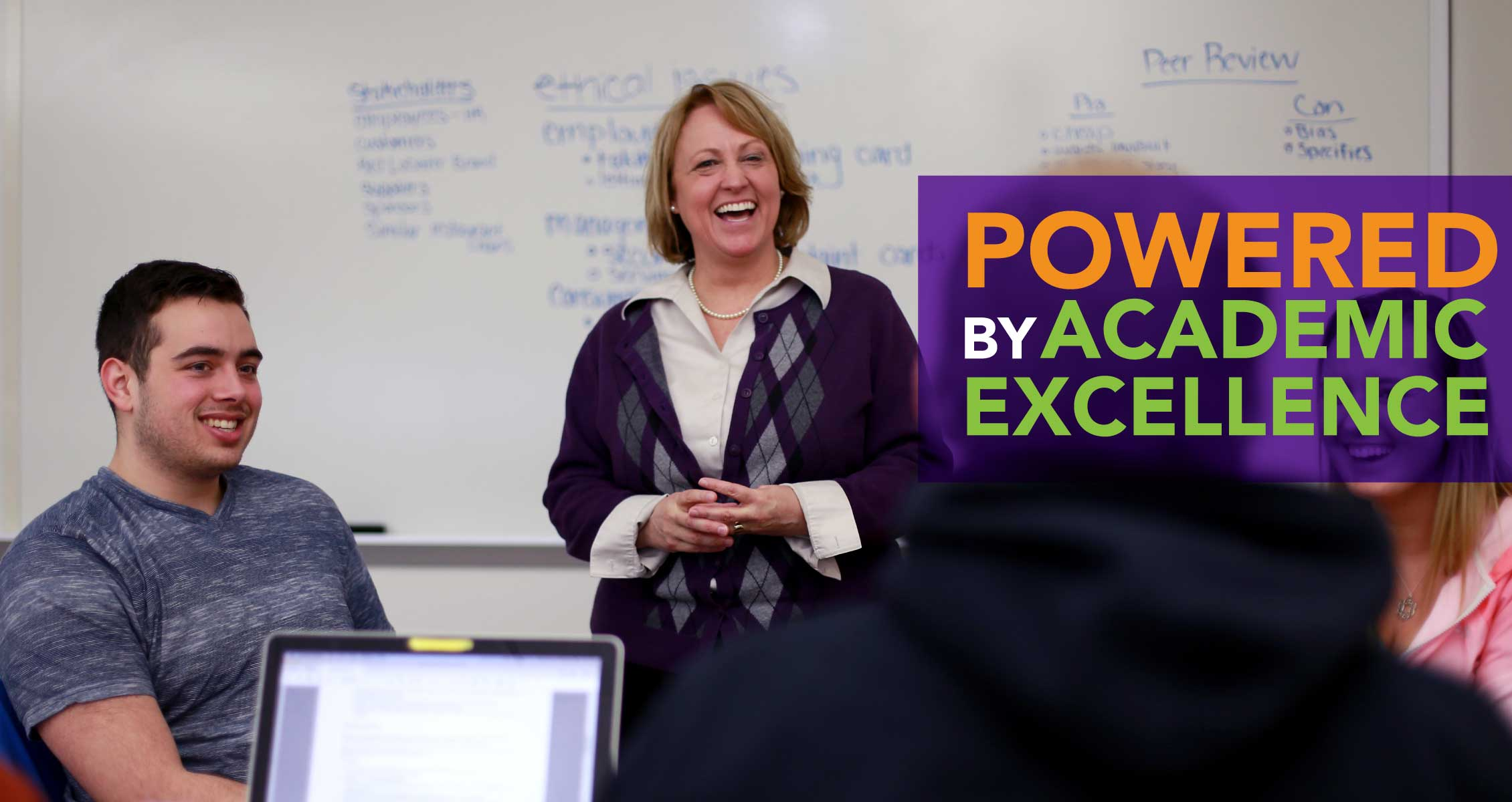 Powerwed By Academic Excellence: Instructor laughing with students in class