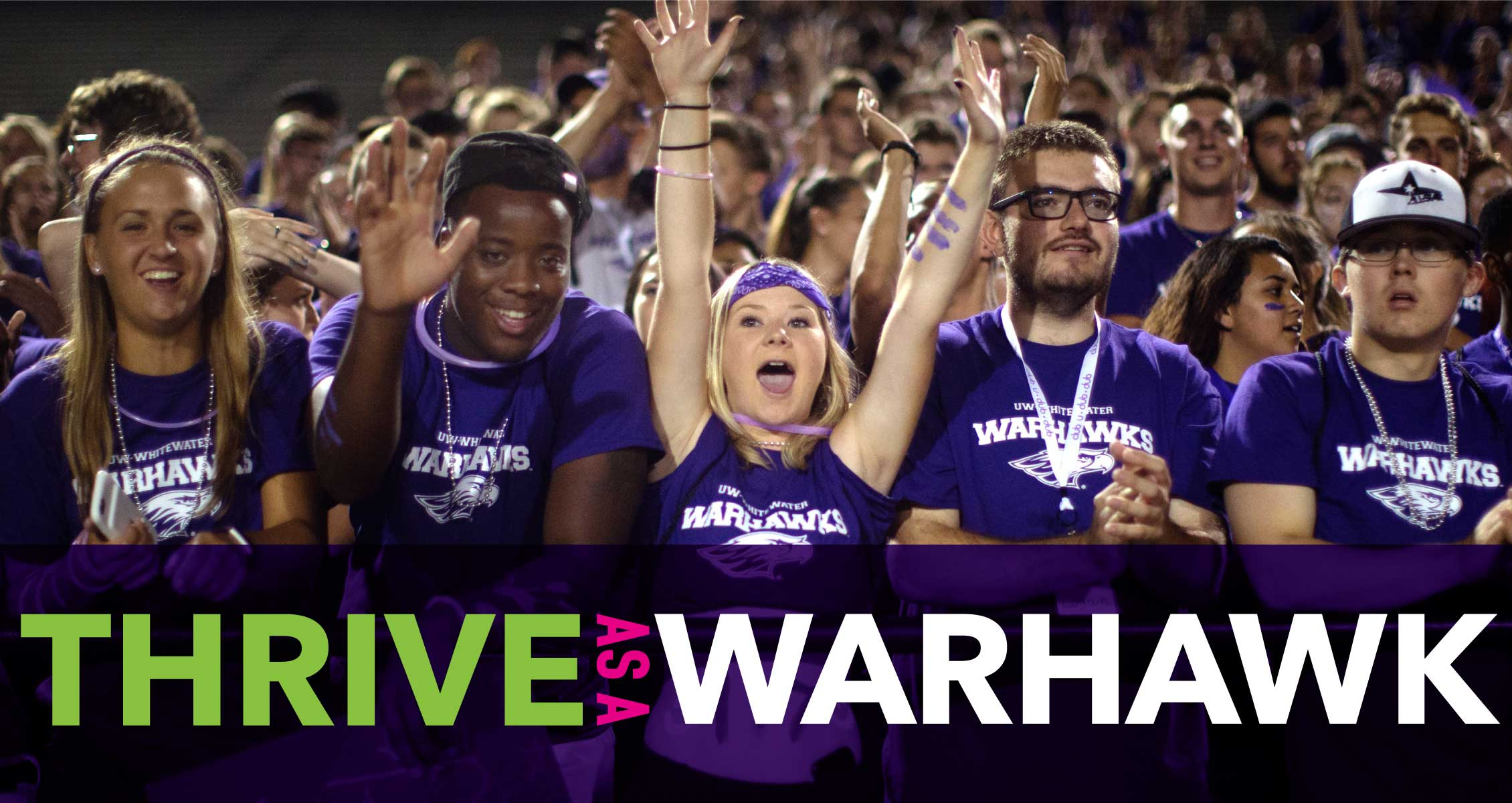 Thrive as a Warhawk: Cheering students in purple in the stands