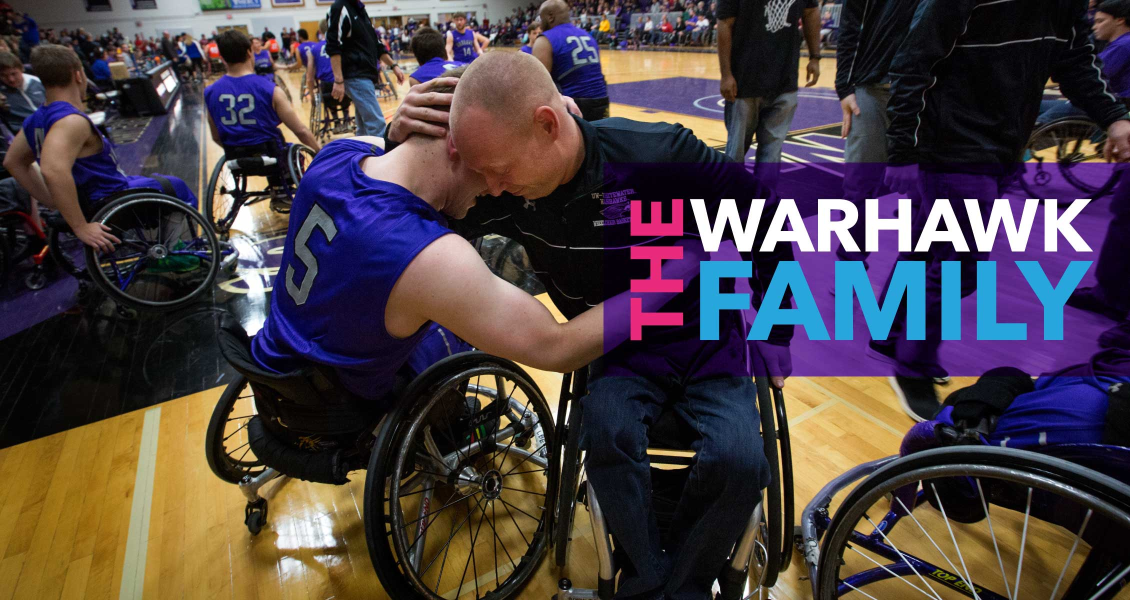The Warhawk Family: Man in wheelchair embraces student in wheelchair on basketball court