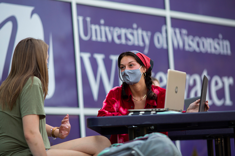 Two people sitting at a table with a UW-Whitewater banner behind them.