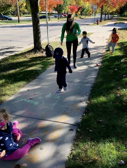 Student with children chalking on a sidewalk.