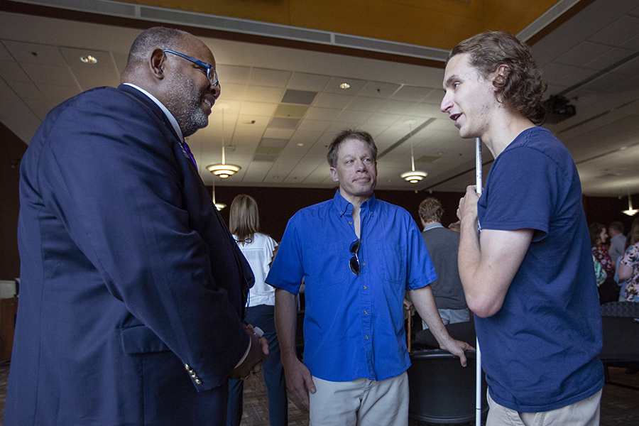 A student with a visual impairment speaks with Chancellor Watson.