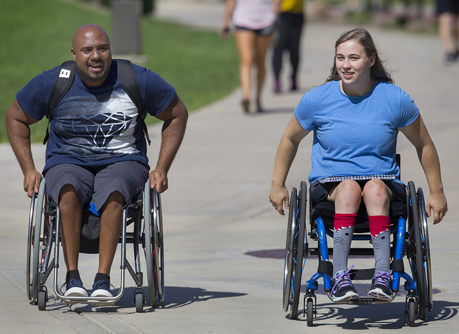 Two students in wheelchairs have a conversation as they cross the mall on the UW-Whitewater campus.
