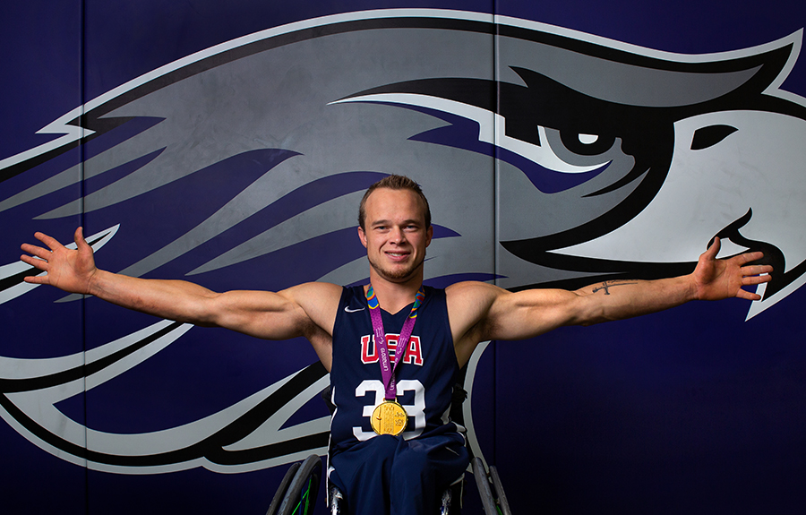 John Boie, member of Team USA, is in front of a Warhawk wall with his arms spread.