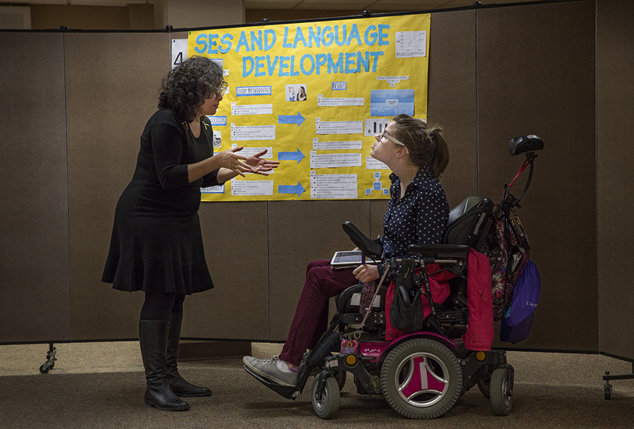 A student in a wheelchair speaks with a faculty member.