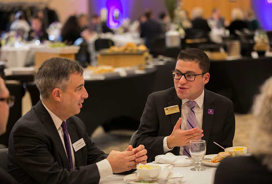 Brian Martinez, Warhawk alum, speaks with UW System Vice President for Finance Sean Nelson in the Hamilton Room of the University Center.