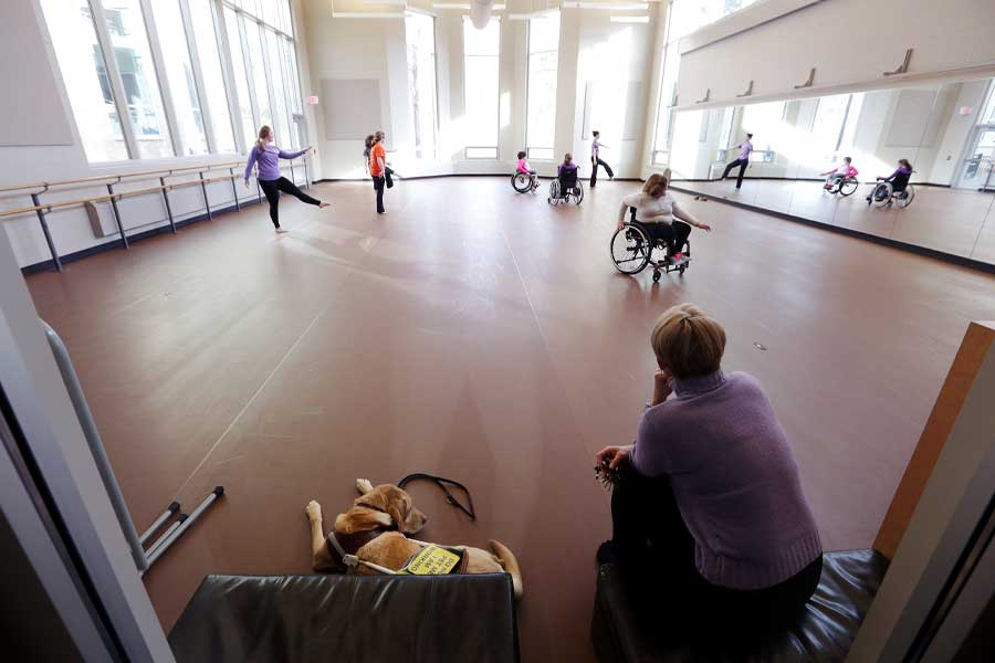 Professor Barb Grubel in a dance studio with several students.