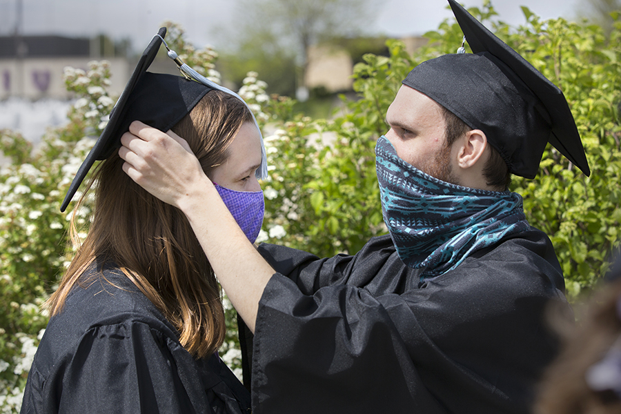 One students helps another student with their graduation cap.