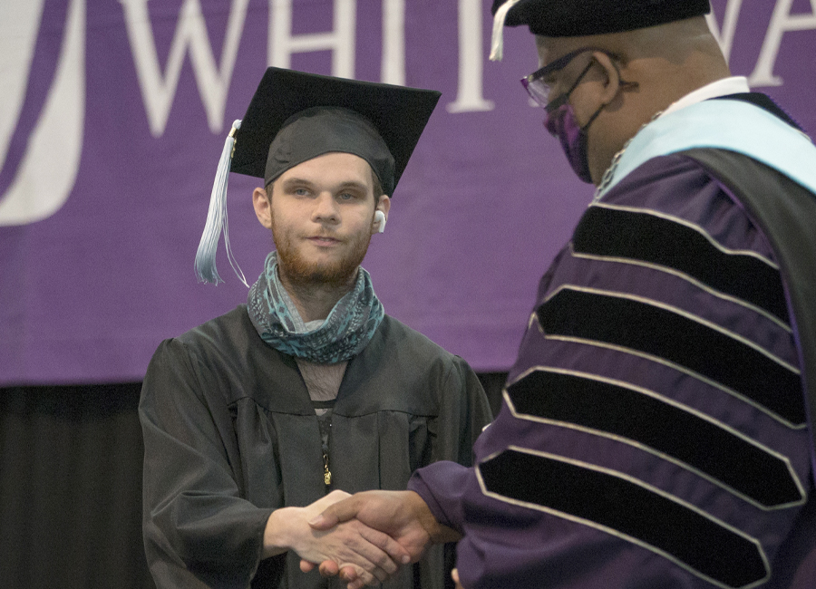 LIFE program participant Sam Craden shakes hands with Chancellor Watson in graduation cap and gown.