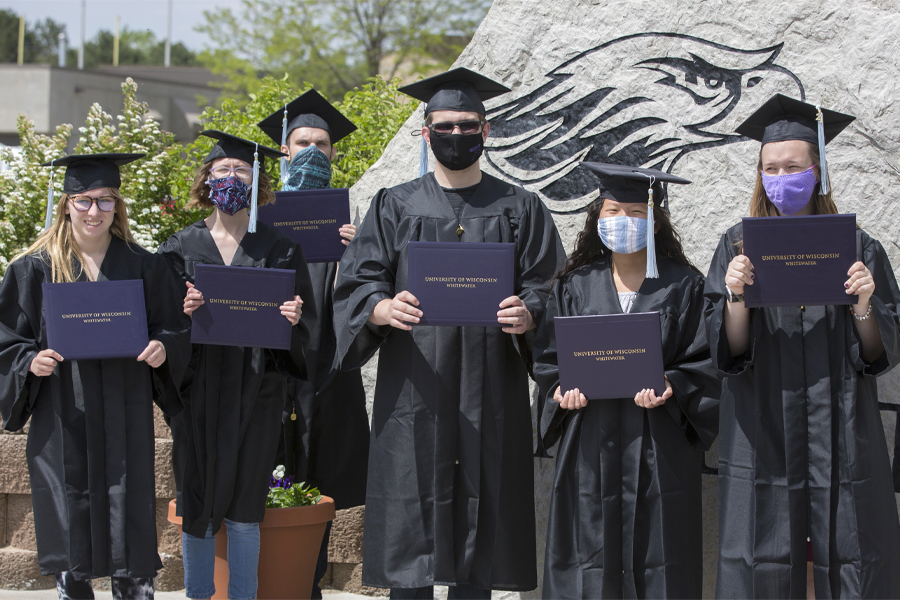Six Warhawks stand outside wearing caps and gowns.