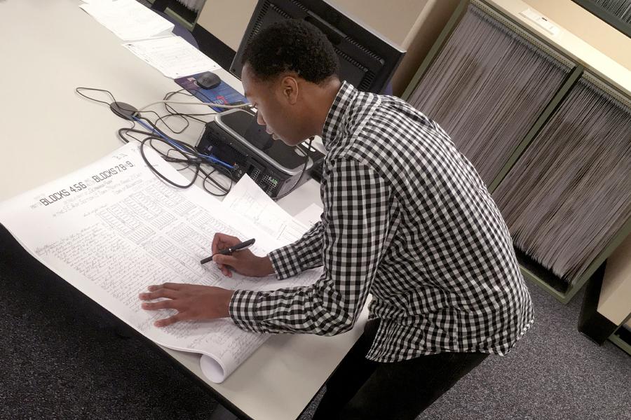 Donovan Hemphill tracing the land genealogy at a desk.