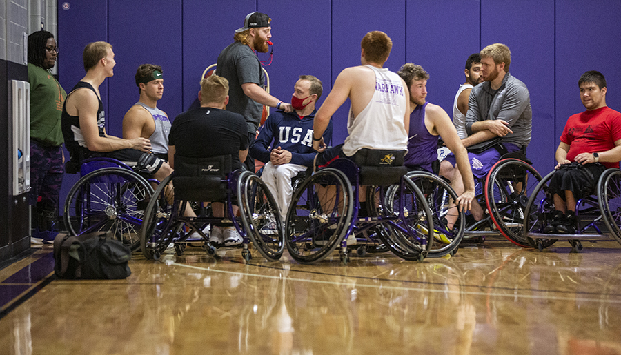 A group of people in the wheelchair basketball gym.