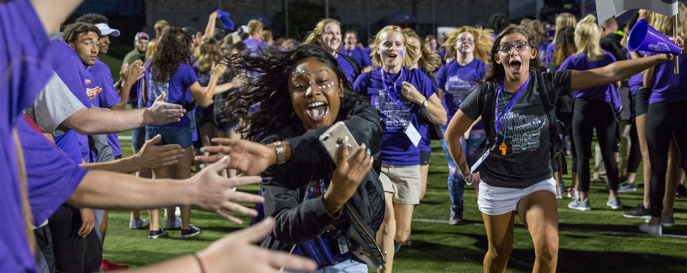First-year students (freshman) and their peer mentors run through a human welcome tunnel of students and staff.