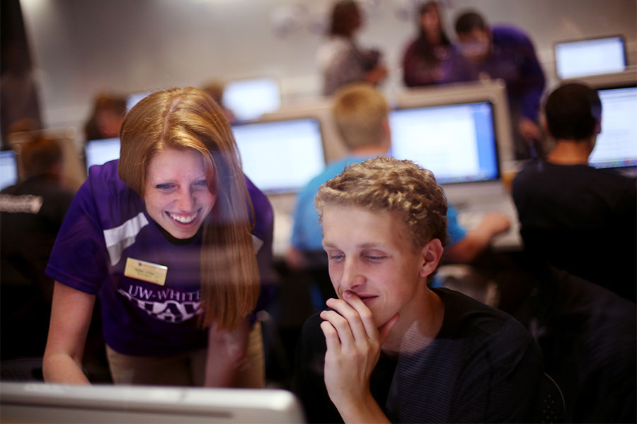 Students work on a computer together on the UW-Whitewater campus.
