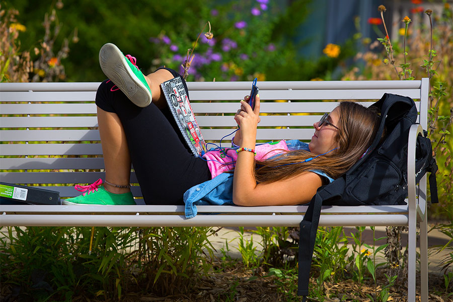 UW-Whitewater student relaxes on a bench outside McGraw Hall on the UW-Whitewater campus.