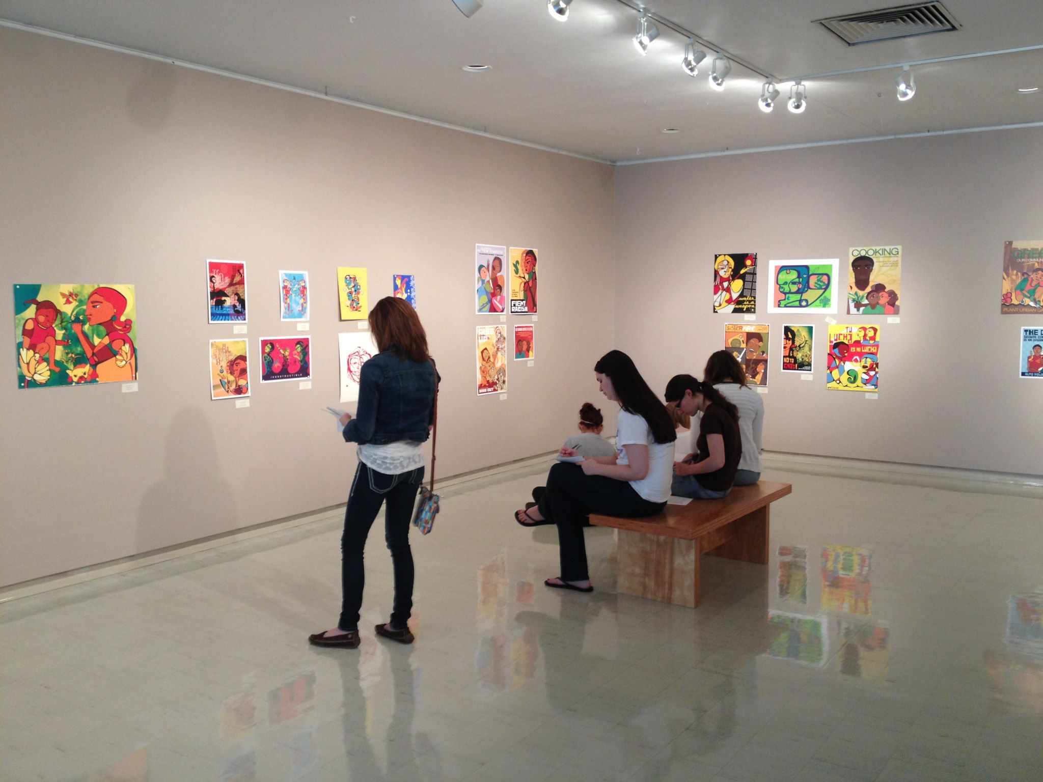 Students writing reviews of solo exhibition of printmaker Favianna Rodriquez in the Crossmann Gallery.