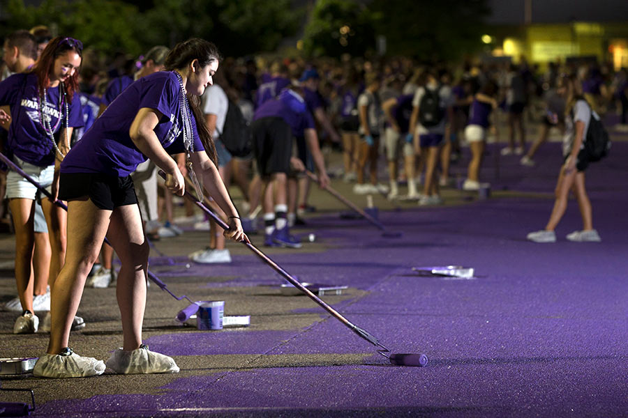 Students paiting the road purple for homecoming