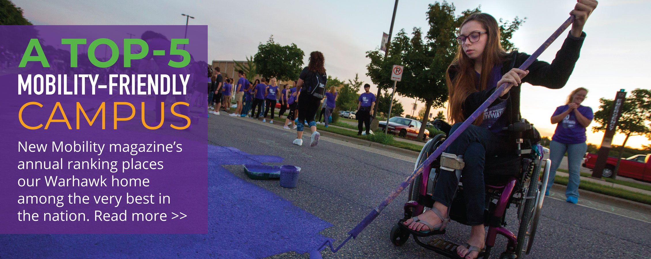 Student in a wheelchair paints Starin Road purple.