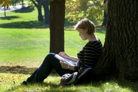 Student studying under a tree for ELA summer programs