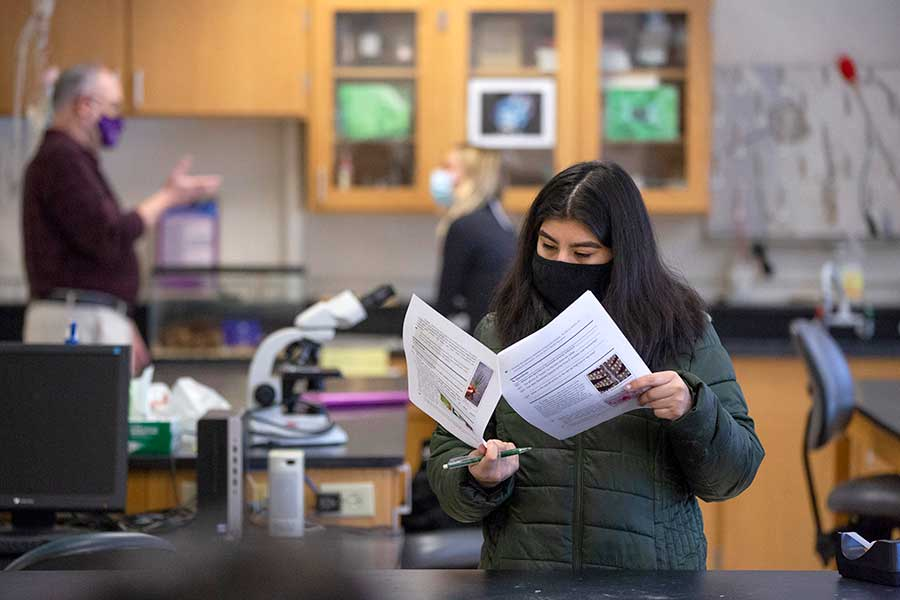 Student standing in a lab reading an in-class exercise.