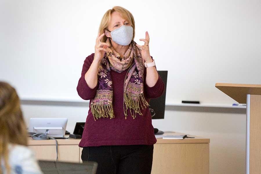Matthews leaning a desk, teaching class.