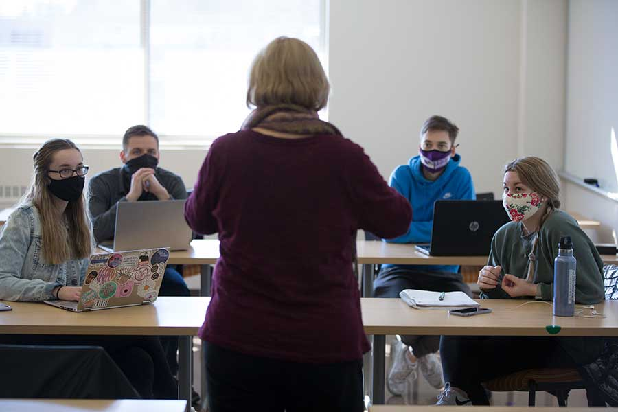 Matthews stands in a classroom full of students with her back to the camera.