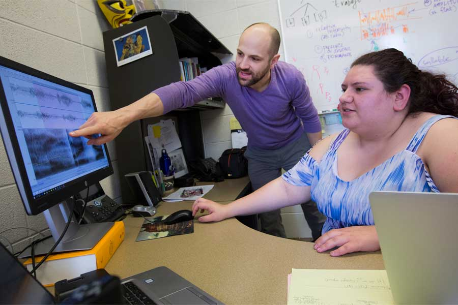 Nate Maddux works with a student at a computer.