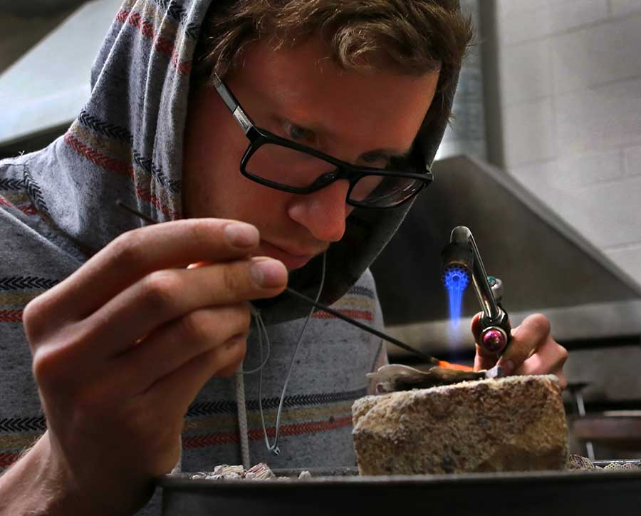 A student creates jewelry with a flame.
