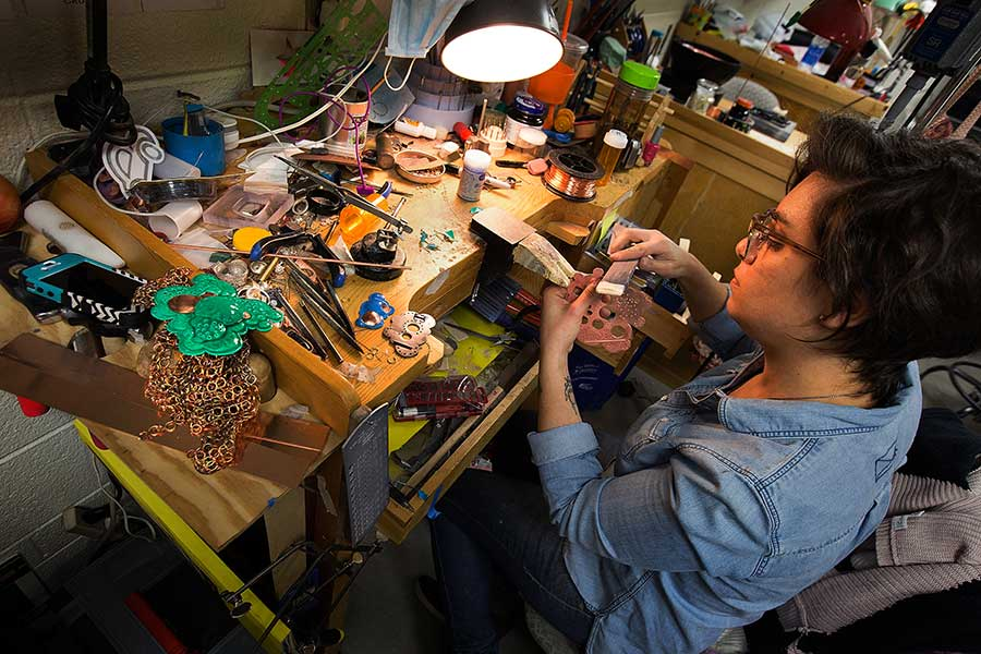 A student works at a wooden table covered in tools and materials.