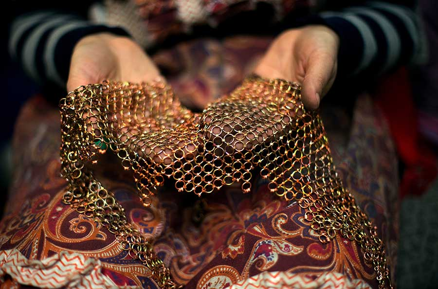 Two hands hold a large, looped, metal necklace.