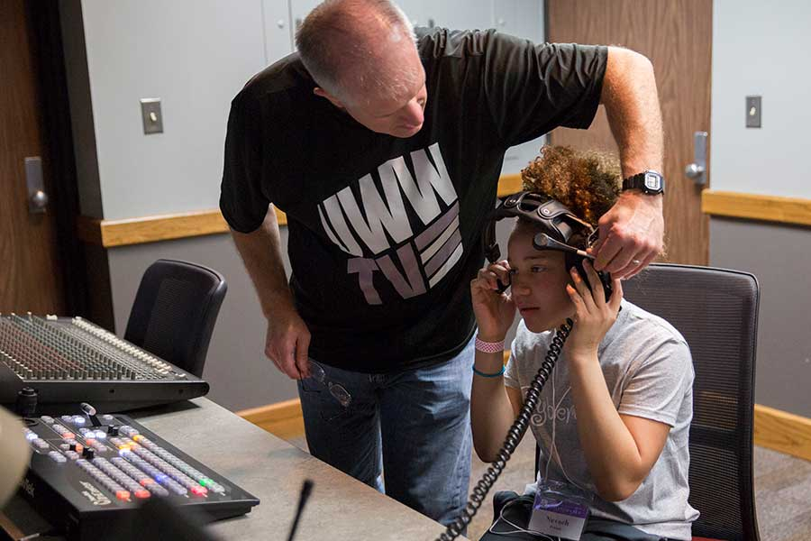 Jim Mead helps a CyberGirlz camper with a headset in the control room.