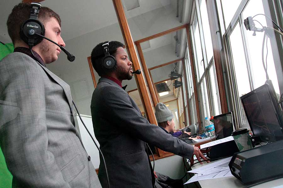 Two students broadcast a football game.