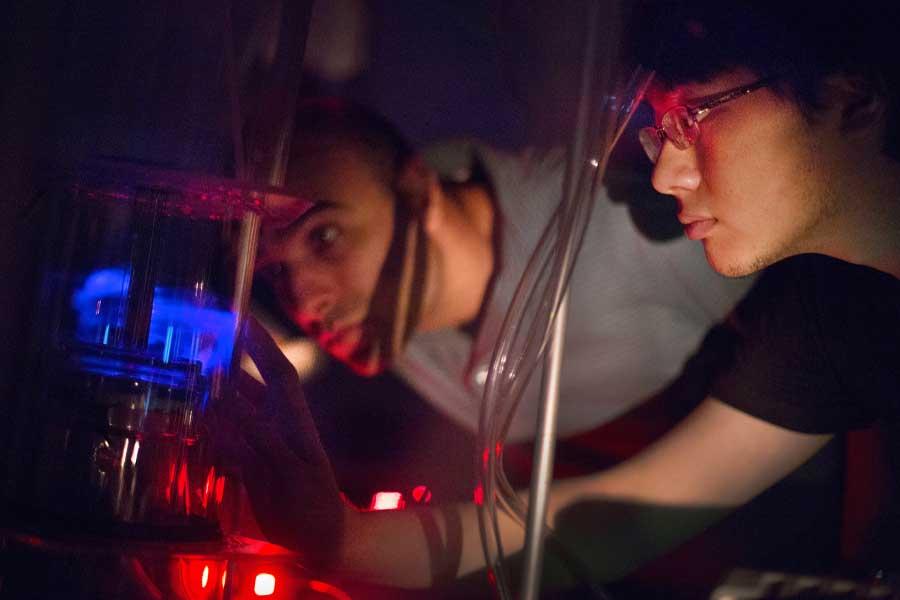 Cold atmospheric plasma glows purple inside a vacuum chamber as Jalal Nawash looks on.