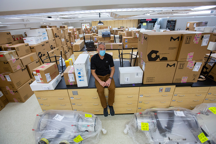 John Ejnik sits on top of boxes with the new equipment and supplies for science labs and undergraduate research donated to the university by MilliporeSigma of Milwaukee.