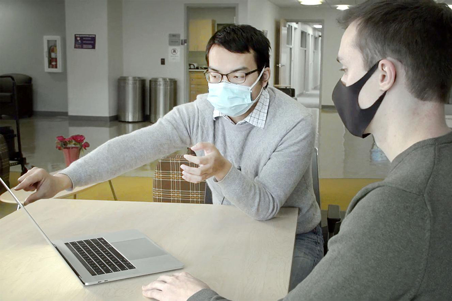 Haijian Sun works with a student on a computer.