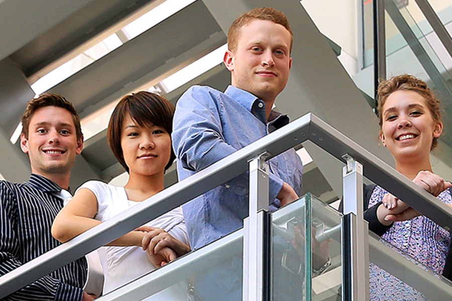 Image: 4 graduate students posing on balcony.