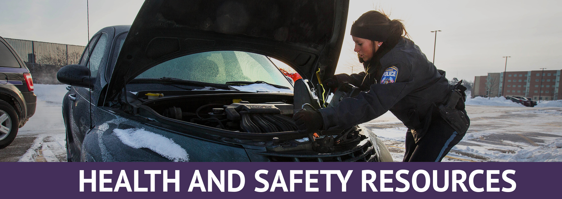 Health and Safety Resources: Police officer checking a car's engine in a snowy parking lot