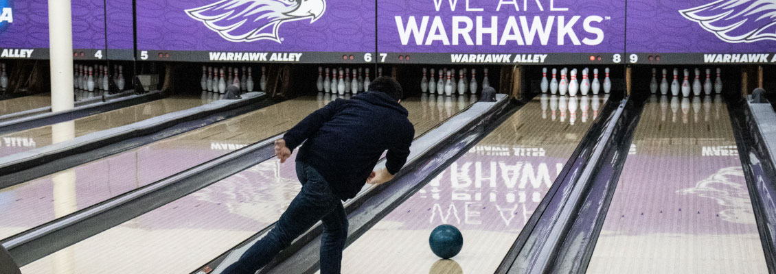 Student bowling in Warhawk Alley